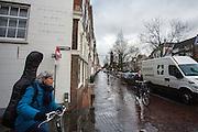 In Utrecht wacht een fietsende vrouw met een gitaarkoffer op haar rug tot een andere fietser voorbij is. Op de muur achter haar staat een gedicht van C.C.S. Crone: &lsquo;In de vertse schitterde een fanfare. Er was weer feest in de Geertestraat.&rsquo;<br /> <br /> In Utrecht a cyling woman with a guitar at her back waits for another cyclists to pass.