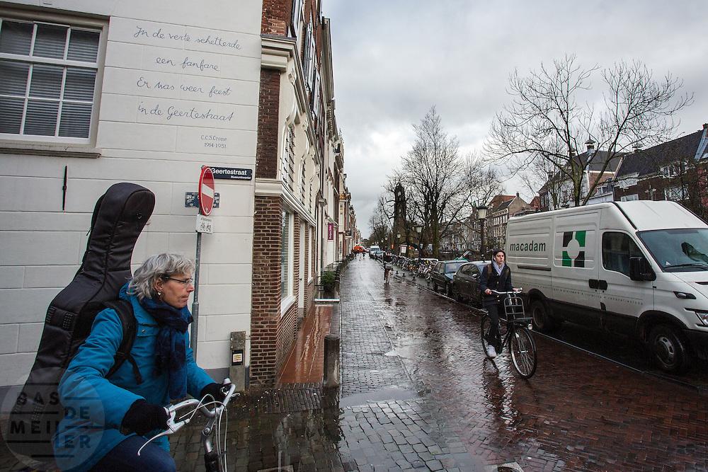 In Utrecht wacht een fietsende vrouw met een gitaarkoffer op haar rug tot een andere fietser voorbij is. Op de muur achter haar staat een gedicht van C.C.S. Crone: 'In de vertse schitterde een fanfare. Er was weer feest in de Geertestraat.'<br /> <br /> In Utrecht a cyling woman with a guitar at her back waits for another cyclists to pass.