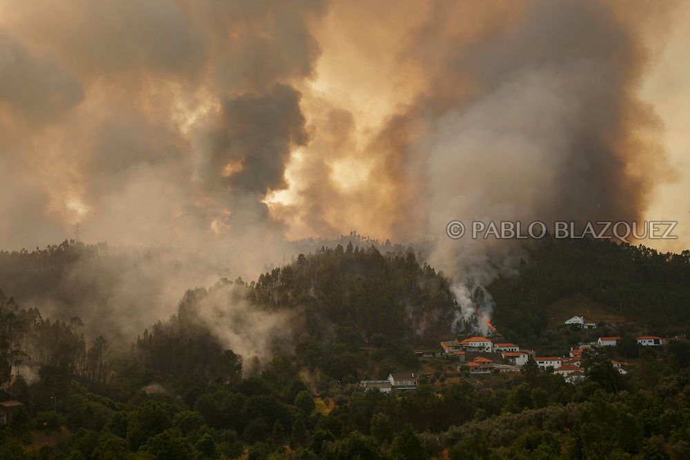 LEIRIA, PORTUGAL - JUNE 20:  A wildfire approaches to Mega Fundeira village after a wildfire took dozens of lives on June 20, 2017 near Picha, in Leiria district, Portugal. On Saturday night, a forest fire became uncontrollable in the Leiria district, killing at least 62 people and leaving many injured. Some of the victims died inside their cars as they tried to flee the area.  (Photo by Pablo Blazquez Dominguez/Getty Images)