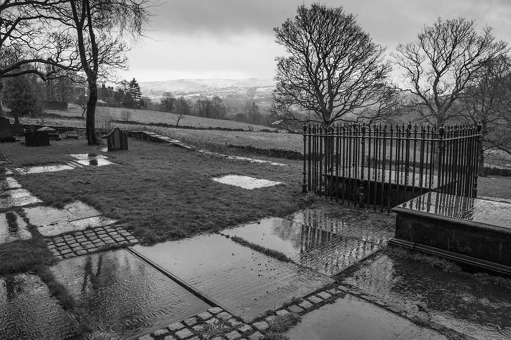 The rain-soaked churchyard of the Parish Church of Holy Trinity, Dobcross, Saddleworth, Greater Manchester.