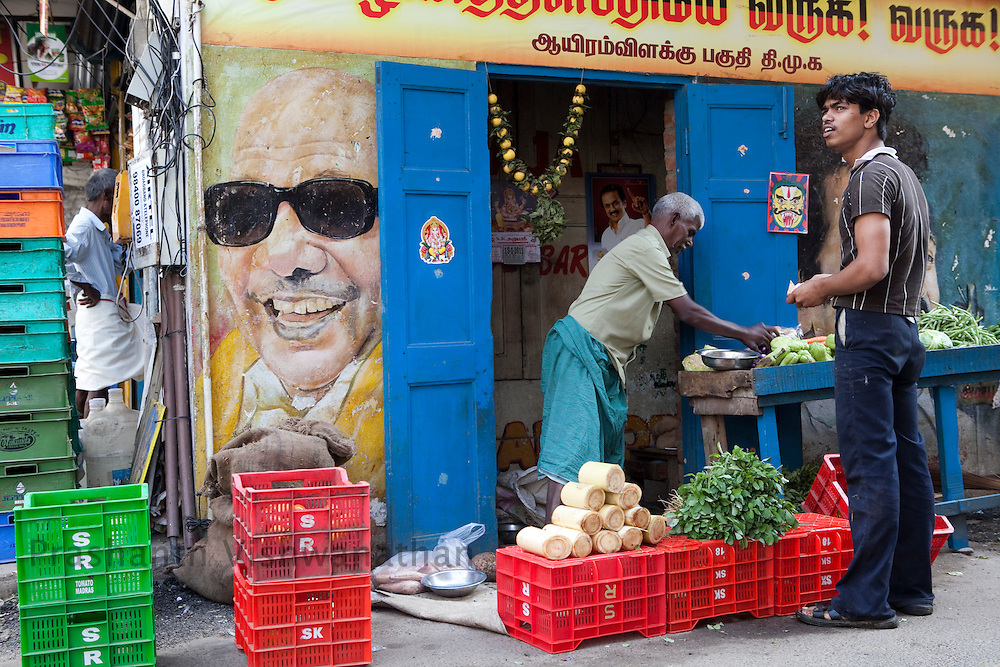A painting of Tamilnadu Chief Minister, M Karunanidhi is seen in a busy vegetable market in Chennai, India, on Thursday, January 13, 2011. Karunanidhi began his career as a screenwriter in the Tamil film industry. Through his wit and oratorical skills he rapidly rose as a popular politician. He was famous for writing historical and social (reformist) stories which propagated the socialist and rationalist ideals of the Dravidian movement to which he belonged. Photographer: Prashanth Vishwanathan/HELSINGIN SANOMAT