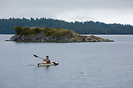 Sea kayakers paddle the Broken Group Islands, Vancouver Island, BC, Canada.