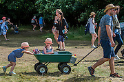 A girl excited by the programme is pushed by her sibling in a trolley - The 2016 Latitude Festival, Henham Park, Suffolk.