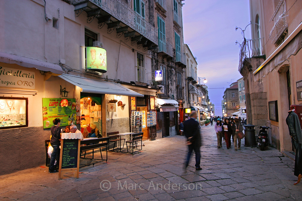 People walking past cafes in the evening in, Tropea, Calabria, Italy