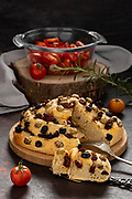 Type of rolled bread with dried tomatoes, capers and olives with cut slice.