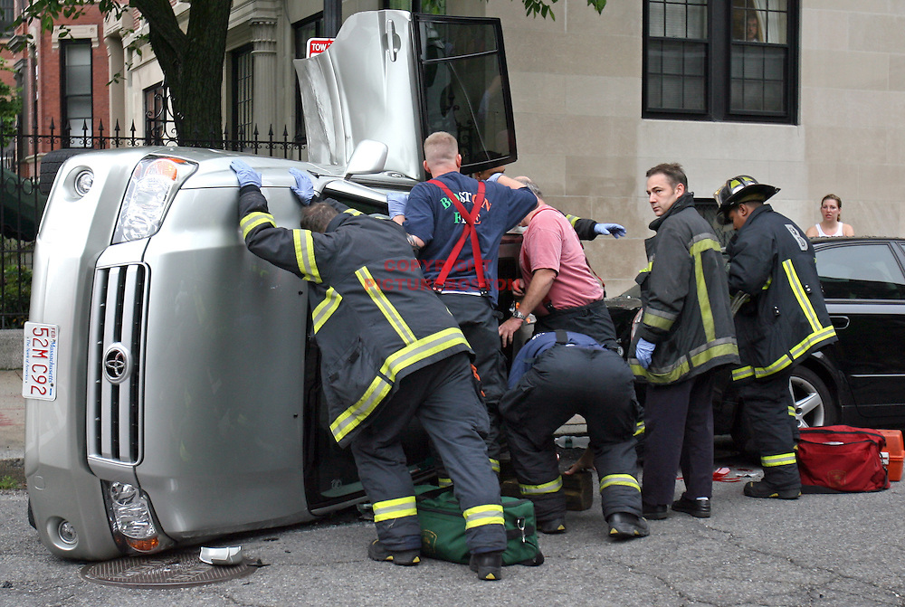 Boston firefighters work to free a victim of this morning's 2 car flip over accident on Commonwealth Ave..