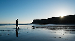 © Licensed to London News Pictures. 11/03/2014<br /> <br /> Saltburn by the Sea, England<br /> <br /> Steve Bulmer and his dog Roxy enjoy a walk along the beach at first light in Saltburn by the Sea in Cleveland.<br /> <br /> Photo credit : Ian Forsyth/LNP