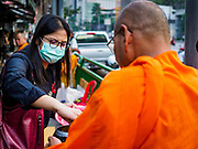 31 JANUARY 2019 - BANGKOK, THAILAND:   A woman wearing a breathing mask because of Bangkok's air pollution presents food to a monk in Bangkok. The Thai government has closed more than 400 schools for the rest of the week because of high levels of pollution in Bangkok. At one point Wednesday, Bangkok had the third highest level of air pollution in the world, only Delhi, India and Lahore, Pakistan were worst. The Thai government has suspended some government construction projects and ordered other projects to take dust abatement measures. Bangkok authorities have also sprayed water into the air in especially polluted intersections to control dust. Bangkok's AQI (Air Quality Index) Thursday morning was 180, which is considered unhealthy for all people.    PHOTO BY JACK KURTZ