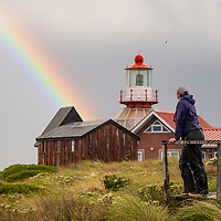 After a storm, a woman watches a rainbow shining over Cape Horn Lighthouse and Stella Maris Chapel on Cape Horn in Chile. Cape Horn (Cabo de Hornos) is the southernmost headland of the Tierra del Fuego archipelago and it marks the northern boundary of the Drake Passage and where the Atlantic and Pacific Oceans meet.