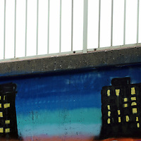 The close-up of street art on a bridge with railings.