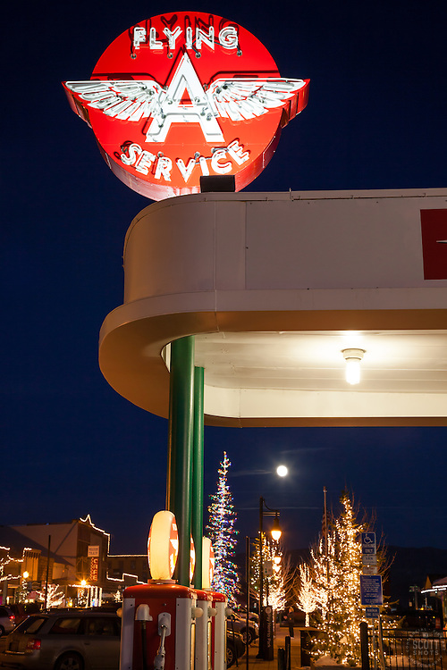 """The Flying A in Truckee 2"" - Photograph of the Flying A in Downtown Truckee with a moon and Christmas lights in the background."