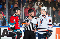 KELOWNA, BC - OCTOBER 12:  Kyle Topping #24 of the Kelowna Rockets and Connor Zary #18 of the Kamloops Blazers speak to referee Ryan Benbow during a time out at Prospera Place on October 12, 2019 in Kelowna, Canada. (Photo by Marissa Baecker/Shoot the Breeze)