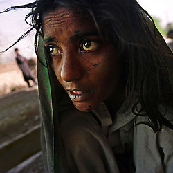 Far From Home - Perveen, sitting amongst the shallow graves of former addicts in Pakistan's northwest Tribal Areas, is watched by the local drug dealers, left, as she prepares her next fix. Perveen, 35 and the daughter of a Punjabi politician, has been abandoned by her family...