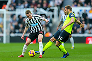 Sean Longstaff (#36) of Newcastle United shields the ball from the challenge of Laurent Depoitre (#20) of Huddersfield Town during the Premier League match between Newcastle United and Huddersfield Town at St. James's Park, Newcastle, England on 23 February 2019.
