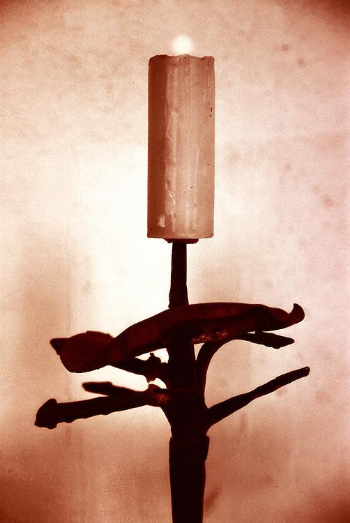 Large candle burning on old cadlestick