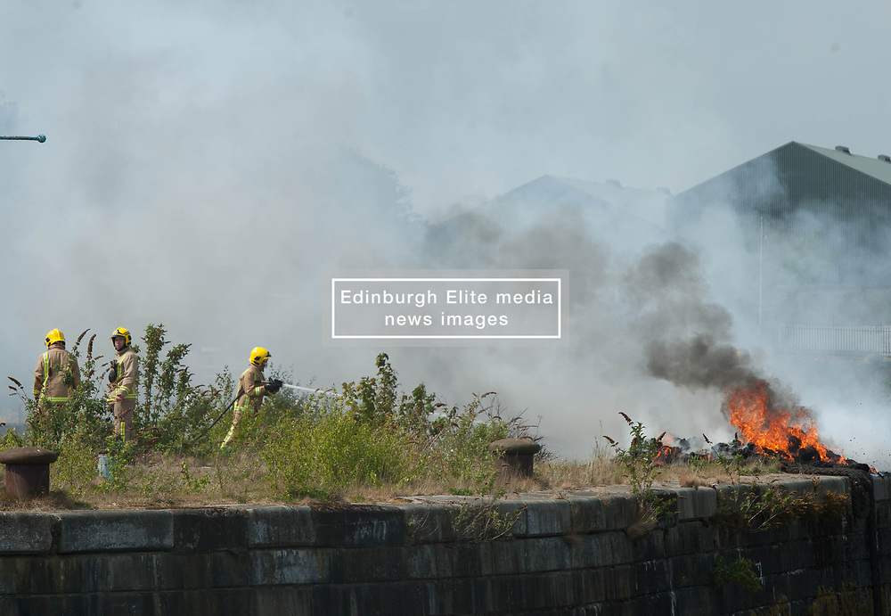 Fire Fighthers arrive to extinguish a fire on waste ground behind the Science Centre in Glasgow, Angie Isac | EEm Thursday 11 May 2017