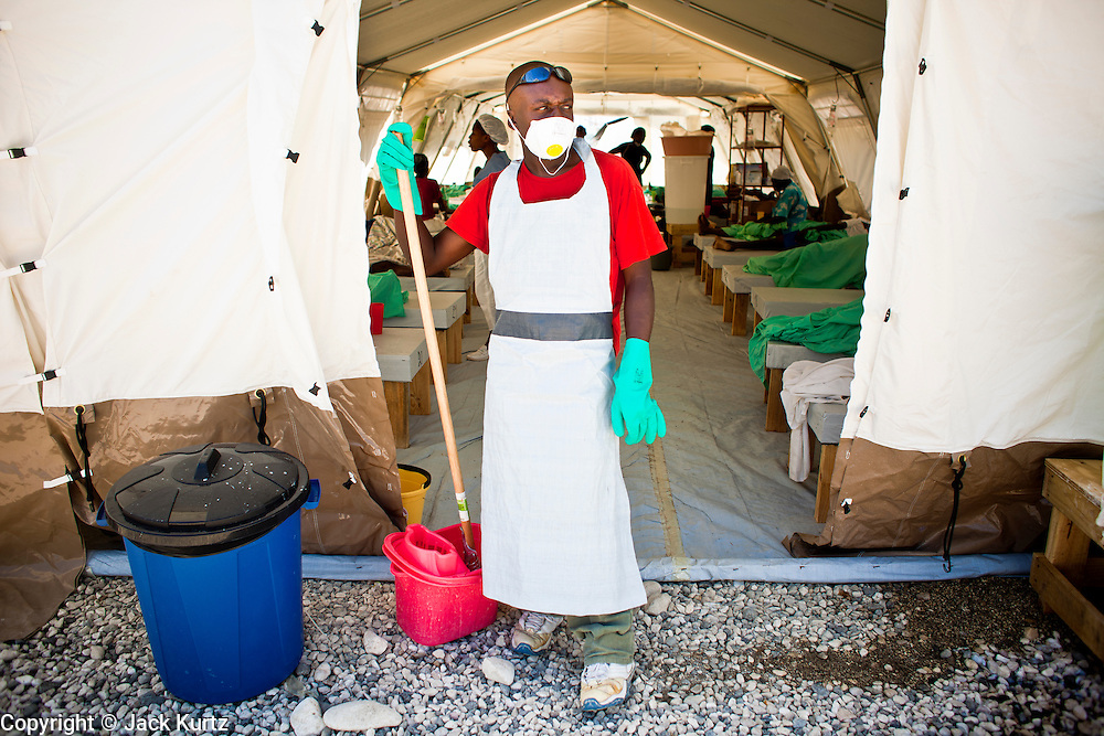 19 NOVEMBER 2010 - PORT-AU-PRINCE, HAITI:  A decontamination worker in front of a tent at a Medicins Sans Frontieres (MSF - Doctors Without Borders) cholera treatment center near the airport in Port-au-Prince. Cite Soleil, a sprawling slum area in PAP is ground zero for the cholera epidemic in the Haitian capital. An outbreak of cholera in northern Haiti about a month ago has spread across the nation. Tens of thousands of people have been hospitalized and treated for cholera and more than 1,100 have died. Cholera is a water borne illness that causes severe diarrhea and death by dehydration in a matter of hours.        PHOTO BY JACK KURTZ    choleraepidemic