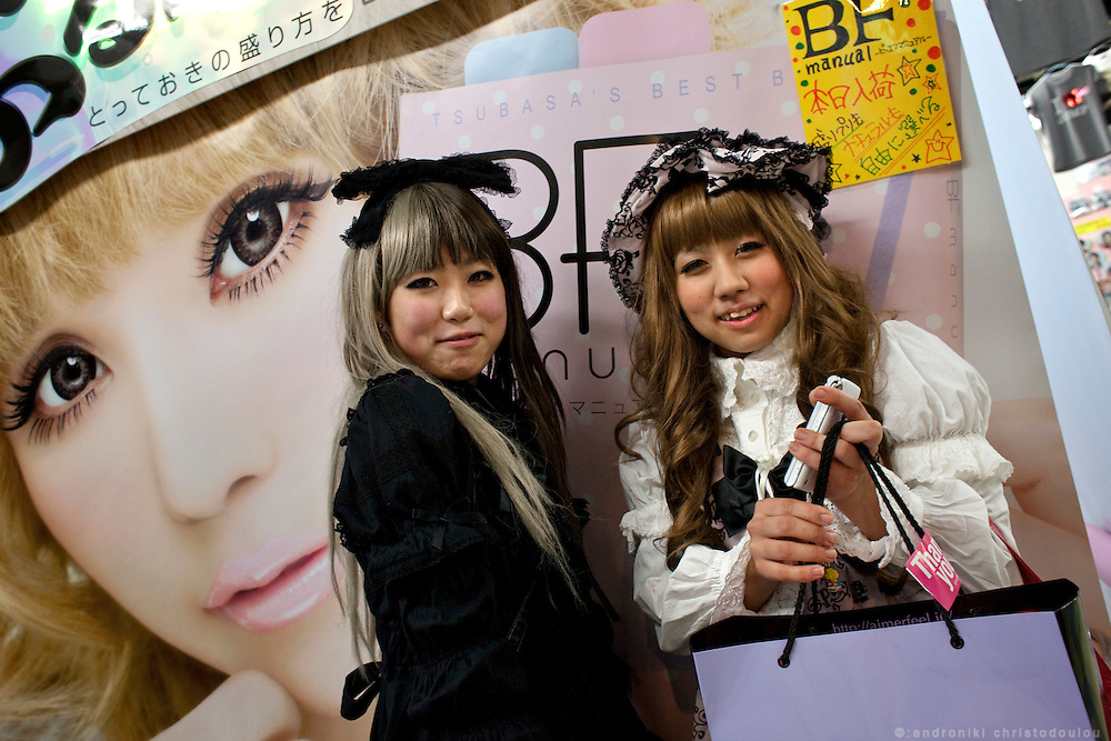 """Japanese girls dressed in """"lolita"""" style, in front of a photo-booth that takes photos where eyes look bigger than normal."""