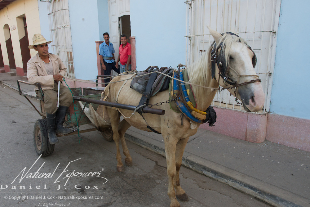 Local Cubans unloading their cart that's pulled by a horse. Trinidad, Cuba.
