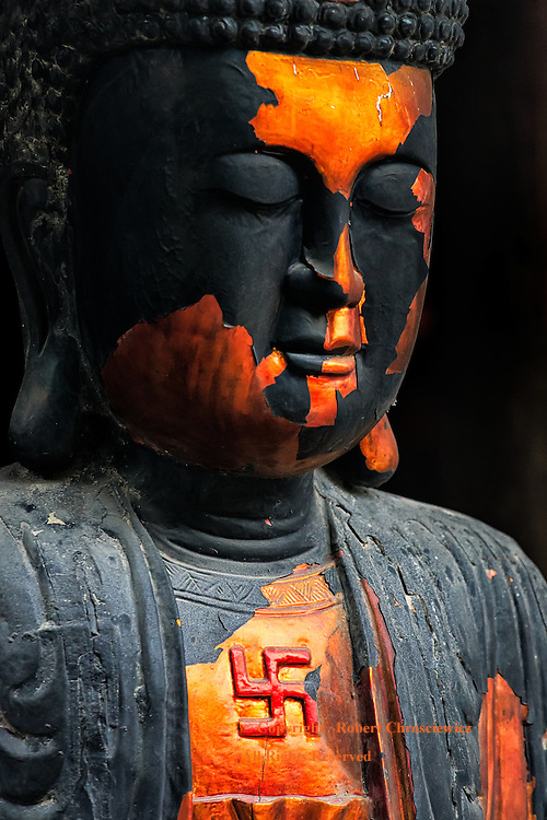 A dynamic black and orange Buddha proudly wears a red Swastika on his chest, Ninh Binh Vietnam.