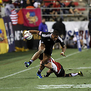NZ 7's Frank Halai breaks a Japan tackle enroute to his first half try at the USA Sevens, Las Vegas, Nevada, USA.  Photo by Barry Markowitz, 2/10/12