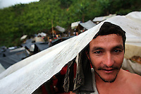 A worker hired by the Colombian government to manually eradicate coca crops shields himself from a light rain under his tent, after a long day of work, in El Campanario, in a remote area of the southern Colombian state of Nariño, on Thursday, June 21, 2007. (Photo/Scott Dalton)