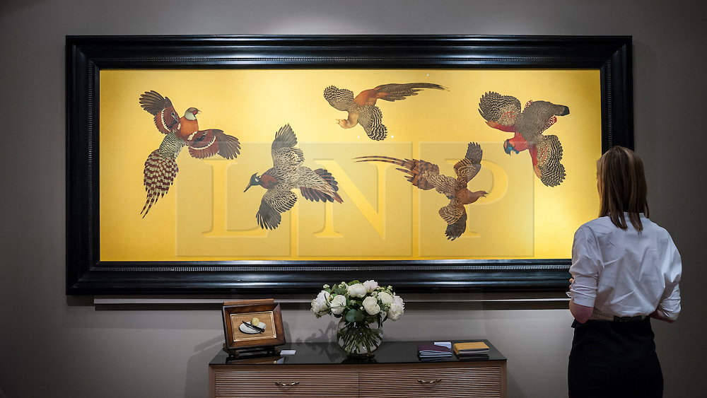 "© Licensed to London News Pictures. 24/06/2015. London, UK.   A visitor looks at Steven Porwal's ""Exotic Pheasants"", at the preview of Masterpiece London, the international cross-collecting Fair for art, antiques and design which takes place at The Royal Hospital Chelsea 25 June to 1 July. Photo credit : Stephen Chung/LNP"