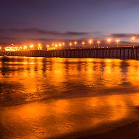 Photo of Huntington Beach Pier at night. Huntington Beach Pier is a registered historic place located along the Pacific Ocean in Orange County California. Photo is high resolution and was taken in 2012.