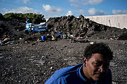 A migrant form Etiopia is seen nearby the shelter where he lives on the top of some industral waste where hundres migrants and refugee are living waiting to cross the channel to UK. Calais. France. FEDERICO SCOPPA