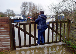 © Licensed to London News Pictures. 26/11/2012. Oxfordshire, UK A woman is cut off from her moored boat by the floodwater from the River Thames in Witney, Newbridge. Flooding on the River Thames today 26th November 2012 in Oxfordshire. Photo credit : Stephen Simpson/LNP