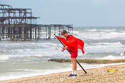 © Licensed to London News Pictures. 08/06/2019. Brighton, UK. A lifeguard places a red flag on the beach in Brighton and Hove as rough seas and strong winds hit the Brighton and Hove beach on Saturday morning in the aftermath of storm Miguel. Photo credit: Hugo Michiels/LNP