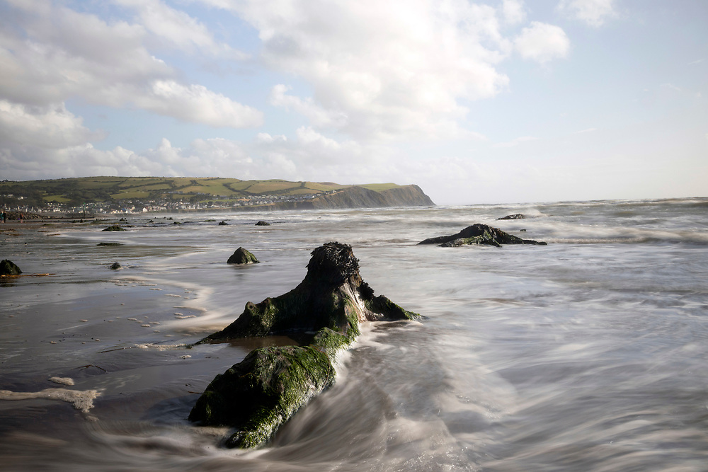 BORTH, WALES, UK 17TH AUGUST 2019 - Long exposure landscape of ancient petrified tree stumps lining the shoreline at Borth Beach, County of Ceredigion, Mid Wales, UK. <br /><br />Appearing at low tide and known as 'the lowland hundred' or the 'sunken hundred,' the ancient stumps have been preserved by the sand and peat for thousands of years and are believed to be connected to the mythical kingdom of Cantre'r Gwaelod. Small areas were uncovered by extreme stormy weather in 2010 and 2014, but the majority were unearthed by Storm Hannah in 2019.