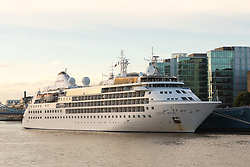 © Licensed to London News Pictures. 01/08/2017. LONDON, UK.  Silver Wind, a huge 514 feet long, 17,400 ton cruise liner seen moored next to HMS Belfast before she leaves London under Tower Bridge this morning after a brief visit, towed backwards by two tugs. Silver Wind carries just 296 passengers and its owner, Silversea claim that the ship has amongst the highest space-to-guest ratios in the cruise ship industry, with the largest suites measuring 1,314 square feet. Tickets cost thousands of pounds, but all guest expenses, even champagne are included in the price. Environmentalists claim thepollutioncreated by giantcruise ships outweigh their economic benefits. The Port of London Authority (PLA) are conducting a work programme during 2017 to monitor air quality and pollution caused by river traffic on the River Thames.  Photo credit: Vickie Flores/LNP