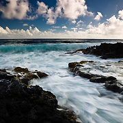 The blue hues of the Pacific Ocean wash in and out along Highway 137 on the Big Island of Hawaii.