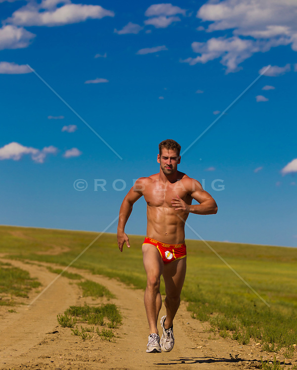 sexy man in red bikini briefs running outdoors on a dirt road