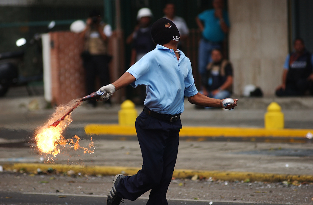 An anti-government protestor still in his school uniform runs down the street before launching a molotov cocktail at members of the Venezuelan army  during the 5th straight day of clashes in Caracas.  The effort to hold a referendum against President Chavez took an expected step backwards when an Electoral Council said there are currently not enough valid signatures to request the referendum.