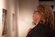 Visitors look at artwork during the opening of the Through the Survivors Lens art exhibit in Trisolini Gallery in Baker Center August, 29, 2019. Photo by Hannah Ruhoff