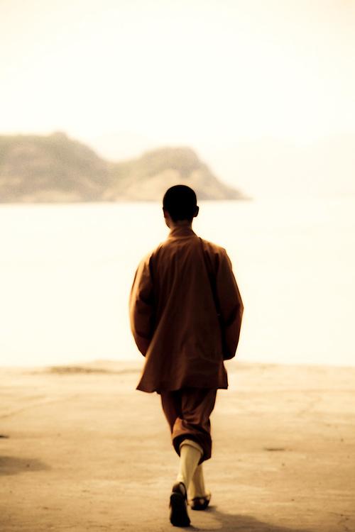 Silhouette of monk walking toward bay in Zhoushan,China
