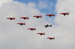 © Licensed to London News Pictures. 13/05/2015. Scampton, UK. A Hurricane from the Battle of Britain Memorial Flight joins the Red Arrows as they train above Scampton in Lincolnshire before the start of their summer display season. Photo credit : Anna Gowthorpe/LNP