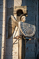 Our Lady of Chartres Cathedral, Chartres, France. Exterior facade - stone statue of an angel holding a sundial.