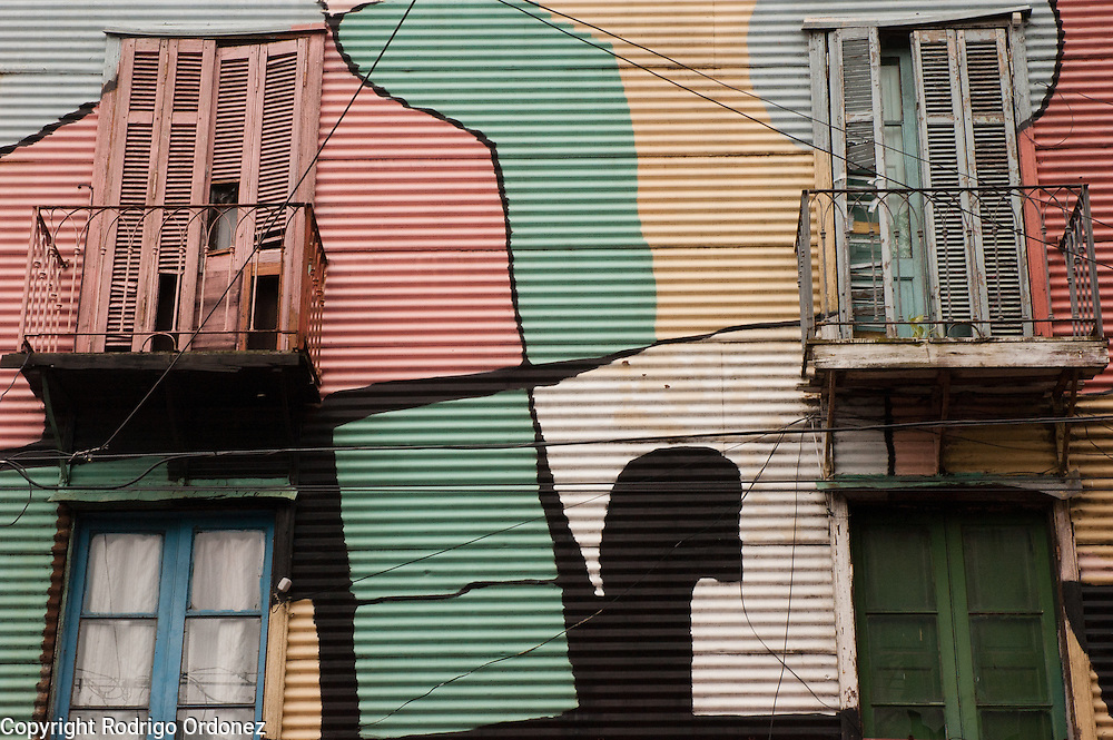View of balconies and windows decorated with paint in Caminito street, in La Boca neighborhood of Buenos Aires, Argentina.<br /> Caminito is a pedestrian street created in the late 1950s by local painter Benito Quinquela Mart&iacute;n and other artist friends to recreate a version of the old immigrant neighborhood of La Boca, using wood and corrugated zinc painted in bright colors. Today, Caminito and the surrounding areas feature cafes, souvenir shops, tango dancers and other street performances aimed to attract tourists.