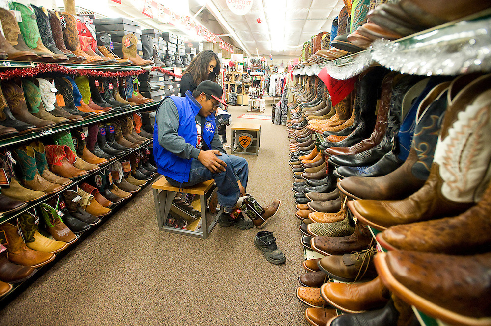 112312       Brian Leddy.Mike Murf tries on boots with his wife at T&R Rope and Feed Friday morning. The store was one of several local stores that opened early for Black Friday.