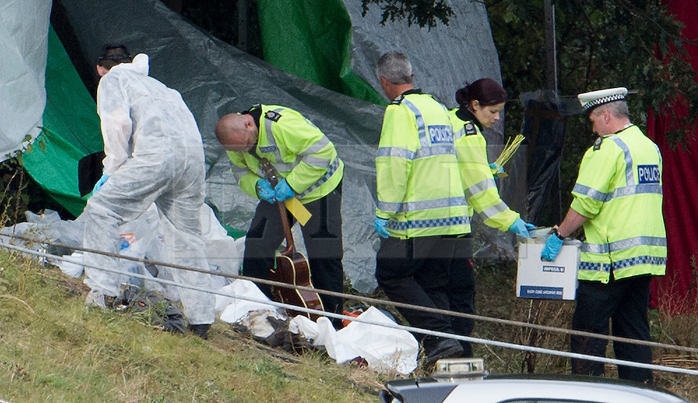 © London News Pictures. 11/09/2012. Hindhead, UK . A police officer examining a guitar amongst other evidence found on the bus which is believed to have been carrying people from the Bestival Festival. The scene of a fatal bus crash on the north bound A3 motorway near Hindhead Tunnel, Hindhead, Surrey on September 11, 2012.Three people were killed and a number of others seriously injured when a coach carrying overturned after crashing into a tree. Photo credit: Ben Cawthra/LNP