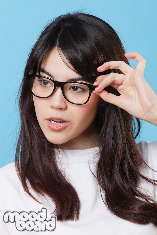 Close-up of mixed race young woman wearing eyeglasses over blue background