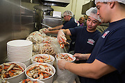 Spring Valley Volunteer Fire Department members David San Jose, Jr. (foreground) and Trung Vo (center) prepare buckets of crab during the Milpitas Chamber of Commerce 21st Annual Auction & Crab Feed at Napredak Hall in San Jose, California, on March 7, 2014. (Stan Olszewski/SOSKIphoto)