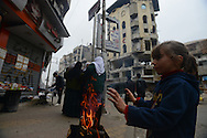Aleppo, Syria, December, 2012. EPISEM RAJEH, 6, warms her hands on the sidewalk in the Alshaar neighborhood of this city. In the background are the ruins of the Dar Al Sheffaa hospital where more then 30 people died during a Syrian government air bombardment nearly a month ago. (Photo by Miguel Juárez Lugo)