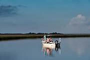 People fish from a small boat in the salt marshes of the Cape Romain National Wildlife Refuge near Charleston, South Carolina. The 66,287 acre National Wildlife Refuge encompass water impoundments, creeks, bays, emergent salt marsh and barrier islands most of which is only accessible by boat.