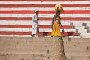 Indian man and woman walking along Rana Mahal Ghat by the Ganges River in City of Varanasi, Benares, Northern India