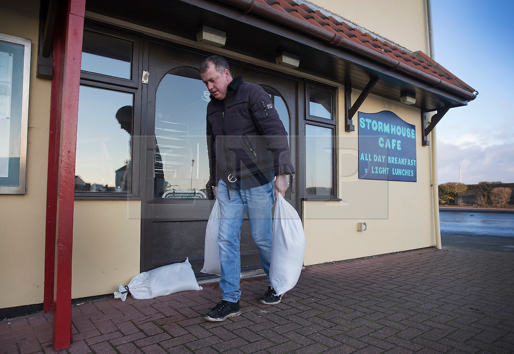 © Licensed to London News Pictures. 14/01/2017. Great Yarmouth, UK. The owner of The Stormhouse Cafe in Gorleston-on-Sea removes sandbags from his doorway after the threat of high tide flooding from the river Yare receded. Hundreds of people are returning to their homes after flood warnings. A change in the wind direction stopped any major flooding to properties on the east coast of England.  Photo credit: Peter Macdiarmid/LNP
