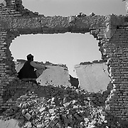 An Afghan civilian sits in a hole in a wall on a pile of rubble adjacent to the main building at Tarnak Farms, the al Qaeda base, training camp and pre 9/11 al Qaeda headquarters in Kandahar, Afghanistan which served as a home to Osama Bin Laden and numerous al Qaeda fighters located outside Kandahar City. It is believed that this base was where the plan for the 9/11 attacks originated, as a result Tarnak Farms was heavily bombed by the United States after September 11, 2001. (Credit Image: © Louie Palu/ZUMA Press).